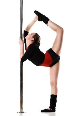 pole dance: Giovane donna danza facendo ginnastica contro uno sfondo bianco in pole Archivio Fotografico