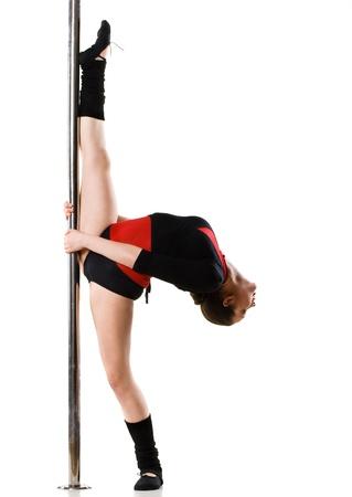 pole dance: Giovane donna pole dance facendo ginnastica contro uno sfondo bianco