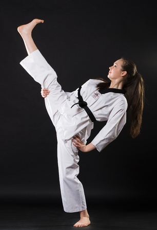 portrait of beautiful martial arts girl in kimono exercising karate kata  against dark background Stock Photo - 10850088