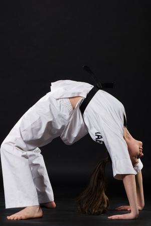 portrait of beautiful martial arts girl in kimono exercising karate kata  against dark background photo