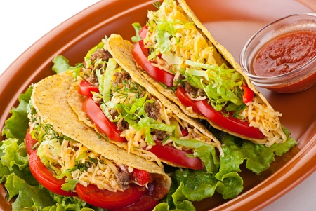 Closeup of beef tacos served with salad and fresh tomatoes salsa on white background photo