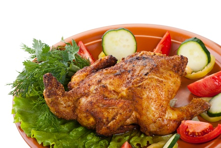 fresh grilled whole chicken with cucumber, raw tomatoes on plate with leaf lettuce isolated over white background