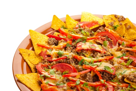 Plate of freshly made spicy nachos with pork, tomato and red pepper on white background