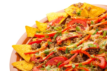 Plate of freshly made spicy nachos with pork, tomato and red pepper on white background photo