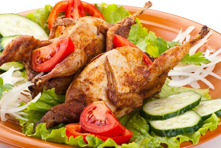 Two fresh grilled whole quail with cucumber, raw tomatoes and onion on plate with leaf lettuce isolated over white background photo