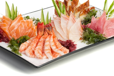 japanese meal: Set of Sashimi on Daikon (White Radish). Garnished with Ginger, Seaweed, Cucumber