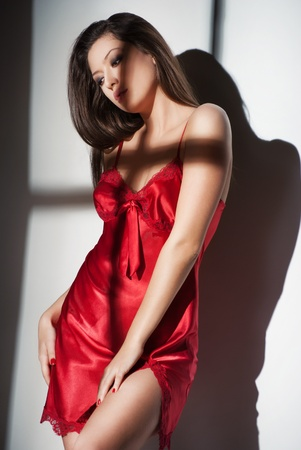 Fashion photo of beautiful woman in red nightdress in light of window Stock Photo