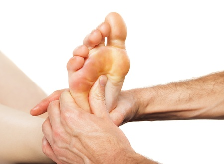 Closeup of foot receiving massage on white photo