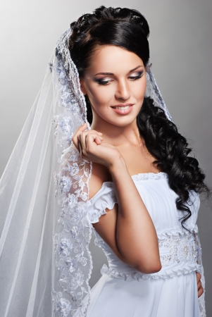beautiful bride is standing in wedding dress on grey background photo