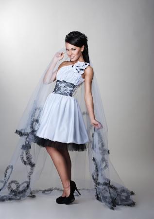 mooie bruid staat in trouwjurk op grijze achtergrond