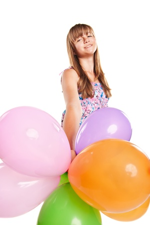 Teenage girl playing with colourful balloons on a white background photo