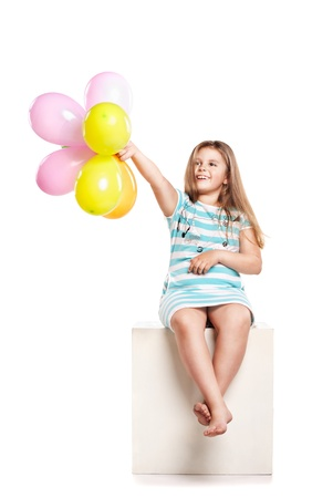 Little girl playing with colourful balloons on a white background photo