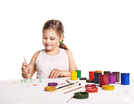 small beautiful girl paints on paper over white background photo