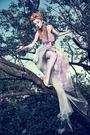 Mooie jonge dame het dragen van elegante witte jurk met rozen staan op de boom in hout Stockfoto