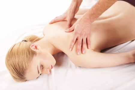 girl getting a massage - hands massaging her back - A pretty woman getting a shoulder and back massage photo