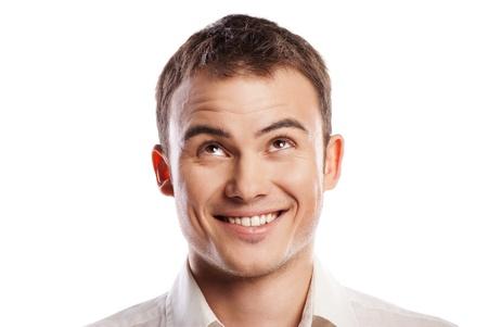 Knappe lachende jonge man kijkt omhoog over witte achtergrond Stockfoto