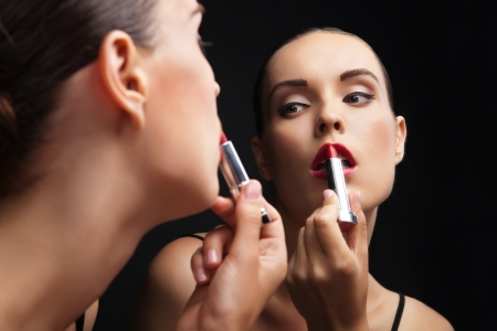 Beautiful sexy young woman hold lipstick near a mirror over black background photo