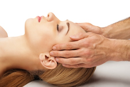 head rest: Young bright woman receiving a head massage in a spa centre