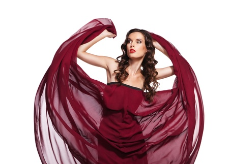 Dancing woman in red dress waving flying on wind flow with long curly hair over white photo