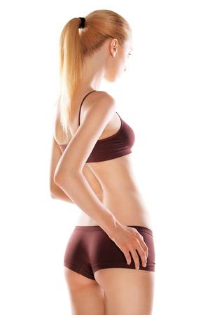 sport wear: Vista trasera de la hermosa mujer rubia cauc�sicos con pelos largos en ropa deportiva, aislados en fondo blanco