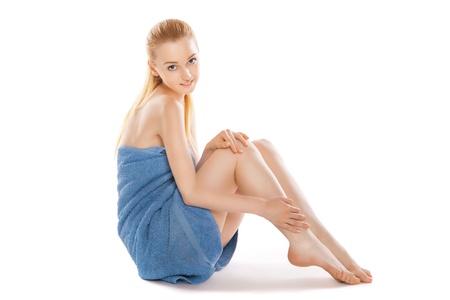 Beautiful young woman in towel sitting on the floor and stroking her beauty legs isolated Stock Photo - 16523448