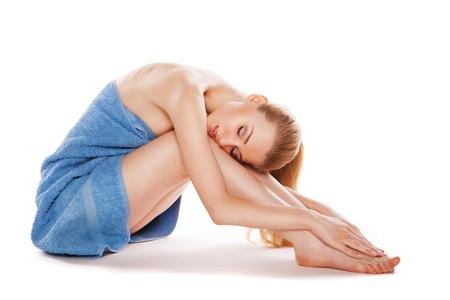 Schöne junge Frau im Handtuch auf dem Boden sitzen und streichelte ihre Schönheit Beine isoliert auf weiß