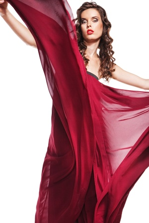woman in red dress waving flying on wind flow with long curly hair photo