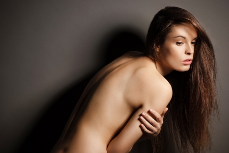 nude pose: Portrait of beautyful naked posing brunette woman with long straight hair on dark grey background Stock Photo