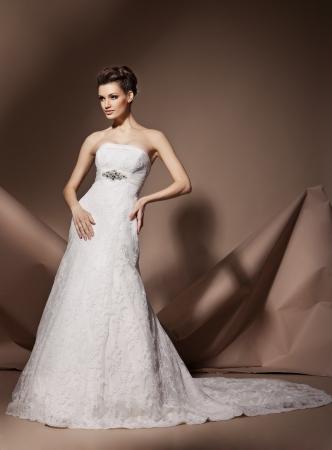 Die schöne junge Frau posiert in einem Hochzeitskleid Standard-Bild - 17850539