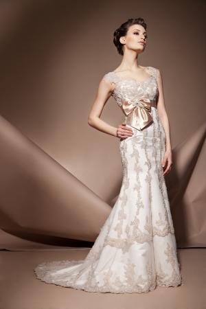 De mooie jonge vrouw die zich in een trouwjurk Stockfoto