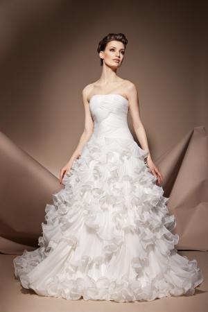 De mooie jonge vrouw poseren in een trouwjurk