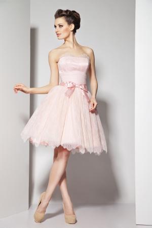 Portret van jonge mooie brunette in een prachtige jurk op witte achtergrond
