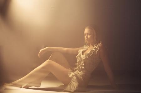 Fashion portrait of blond woman behind transparent textile  photo