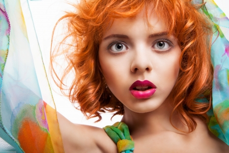 Girl with beautiful red hair and colorful dress and fabric over white background