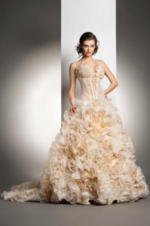 Die schöne junge Frau posiert in einem Brautkleid über grauen Hintergrund Standard-Bild - 18623499