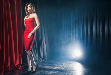 Portret van een mooie vrouw poserend in een rode jurk aan de voorkant van de scènes