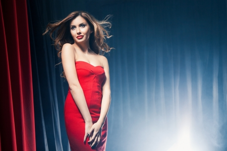 Portrait of a beautiful woman posing in a red dress in front of the scenes