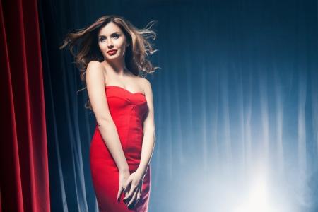 Portret van een mooie vrouw poserend in een rode jurk in de voorkant van de scènes