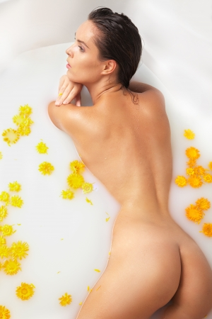 body milk: Attractive  girl enjoys a bath with milk and yellow flowers  Spa body care  Stock Photo