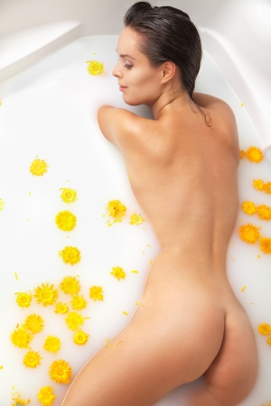naked girl: Attractive  girl enjoys a bath with milk and yellow flowers  Spa body care  Stock Photo