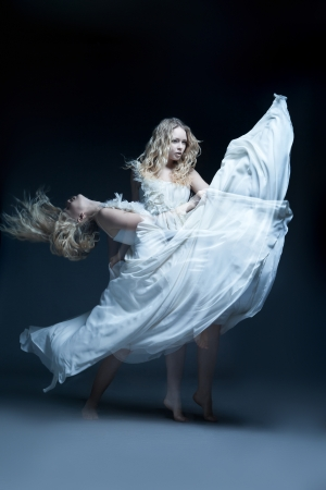 Fine art photo of a dancing beautiful young girl in white wedding dress with multiexposition
