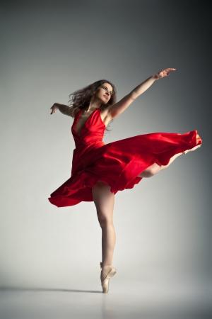 ballet: Hermosa bailarina de ballet joven con un vestido rojo sobre fondo gris oscuro Foto de archivo