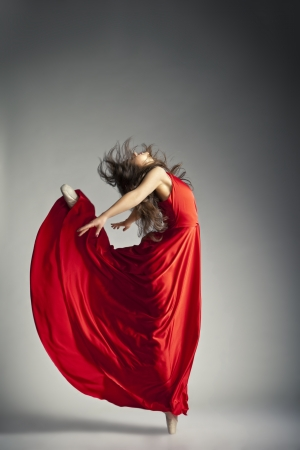 Gorgeous young ballet dancer wearing red dress over dark grey background