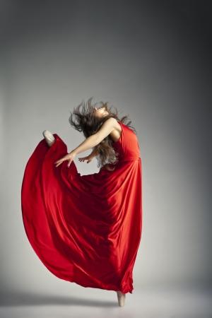 Prachtige jonge balletdanser dragen rode jurk over donkere grijze achtergrond