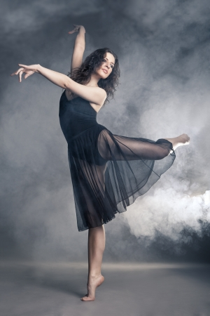 Modern style dancer posing on a studio grey background in fog Stock Photo - 19248516