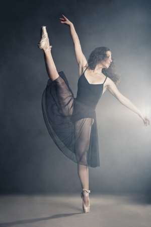 danza clasica: Bailar?n moderno del estilo que presenta en un estudio de fondo gris en la niebla