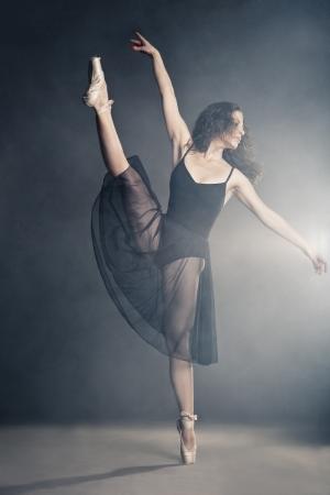 Moderne stijl danser poseren op een studio grijze achtergrond in de mist Stockfoto