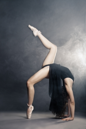 Modern style dancer posing on a studio grey background in fog photo
