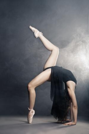 Modern style dancer posing on a studio grey background in fog photo