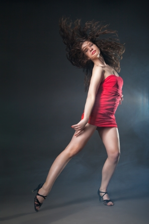 Young sexy dancing woman in red dress with flashes on background with smoke photo